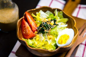A wooden bowl containing green salad with Japanese sesame dressing.