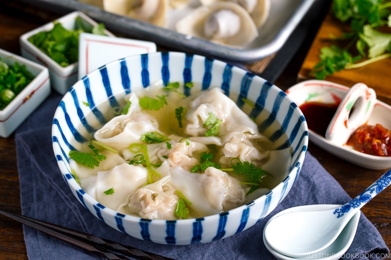 a large bowl containing shrimp and wonton soup along with the condiments.