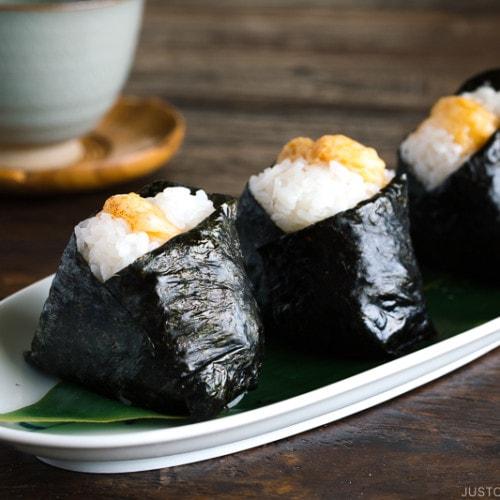 Tenmusu (Shrimp Tempura Rice Balls) on a long Japanese plate.