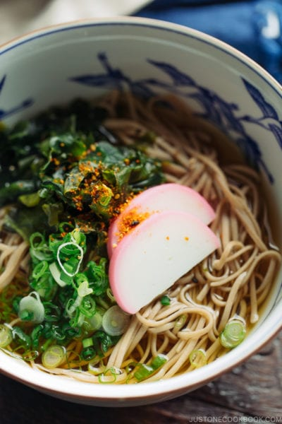 A Japanese bowl containing Toshikoshi Soba Noodle Soup with fish cake and wakame seaweed.