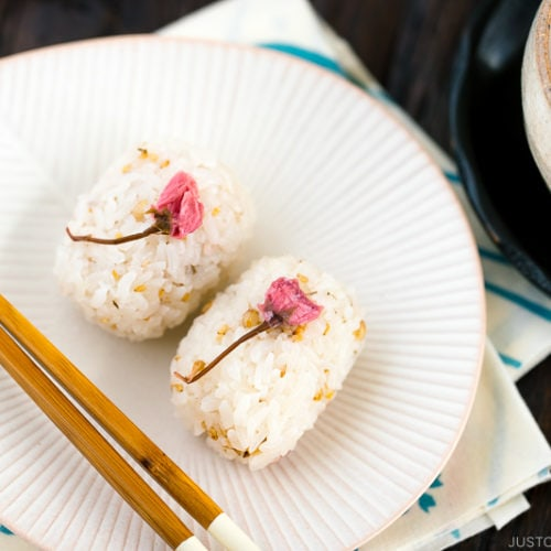 Cherry blossom rice balls on a white plate.