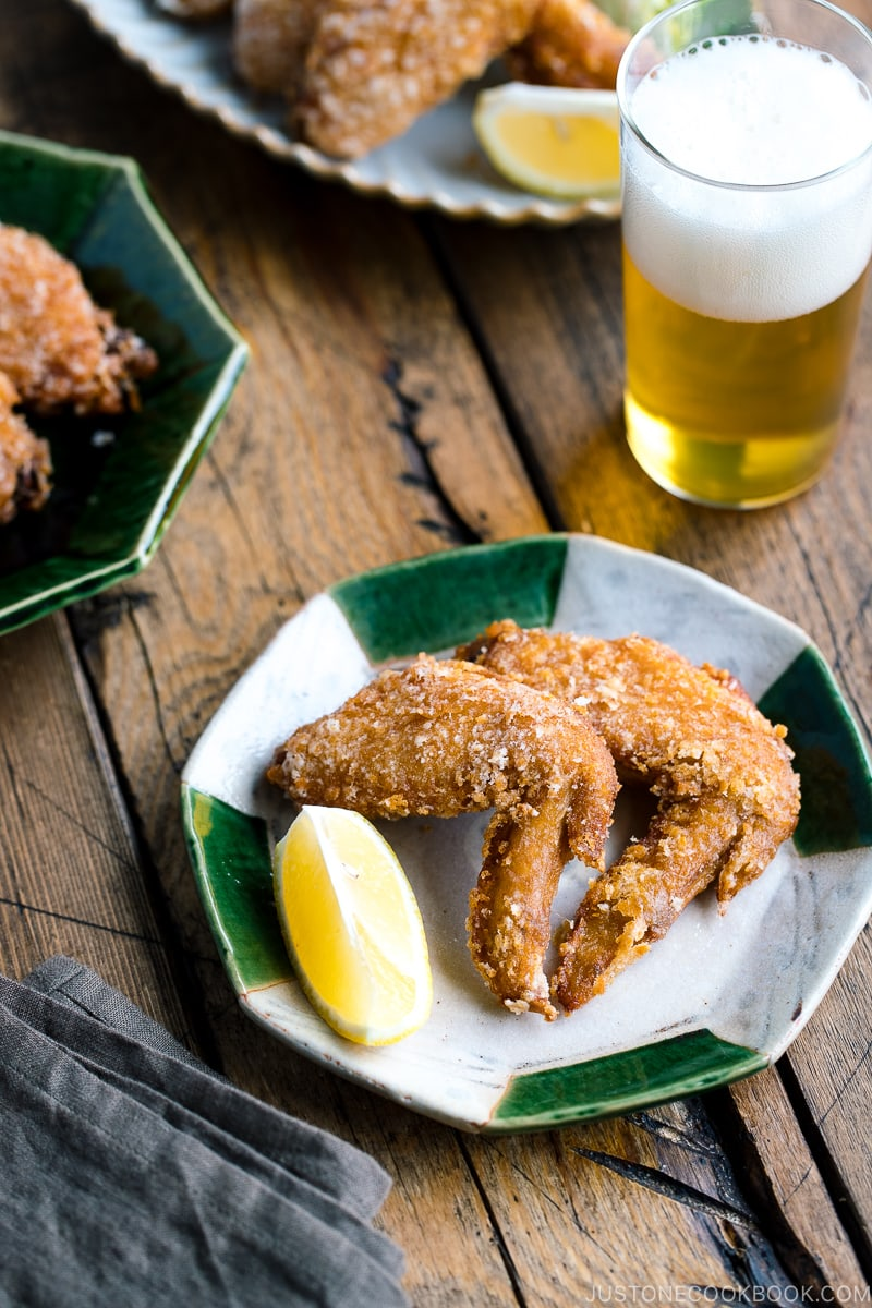 Crispy fried chicken wings on a Japanese plate along with a glass of cold beer.