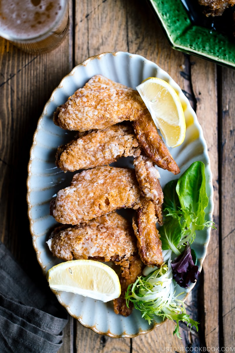 A platter of fried chicken wings garnished with lemon and green salad.