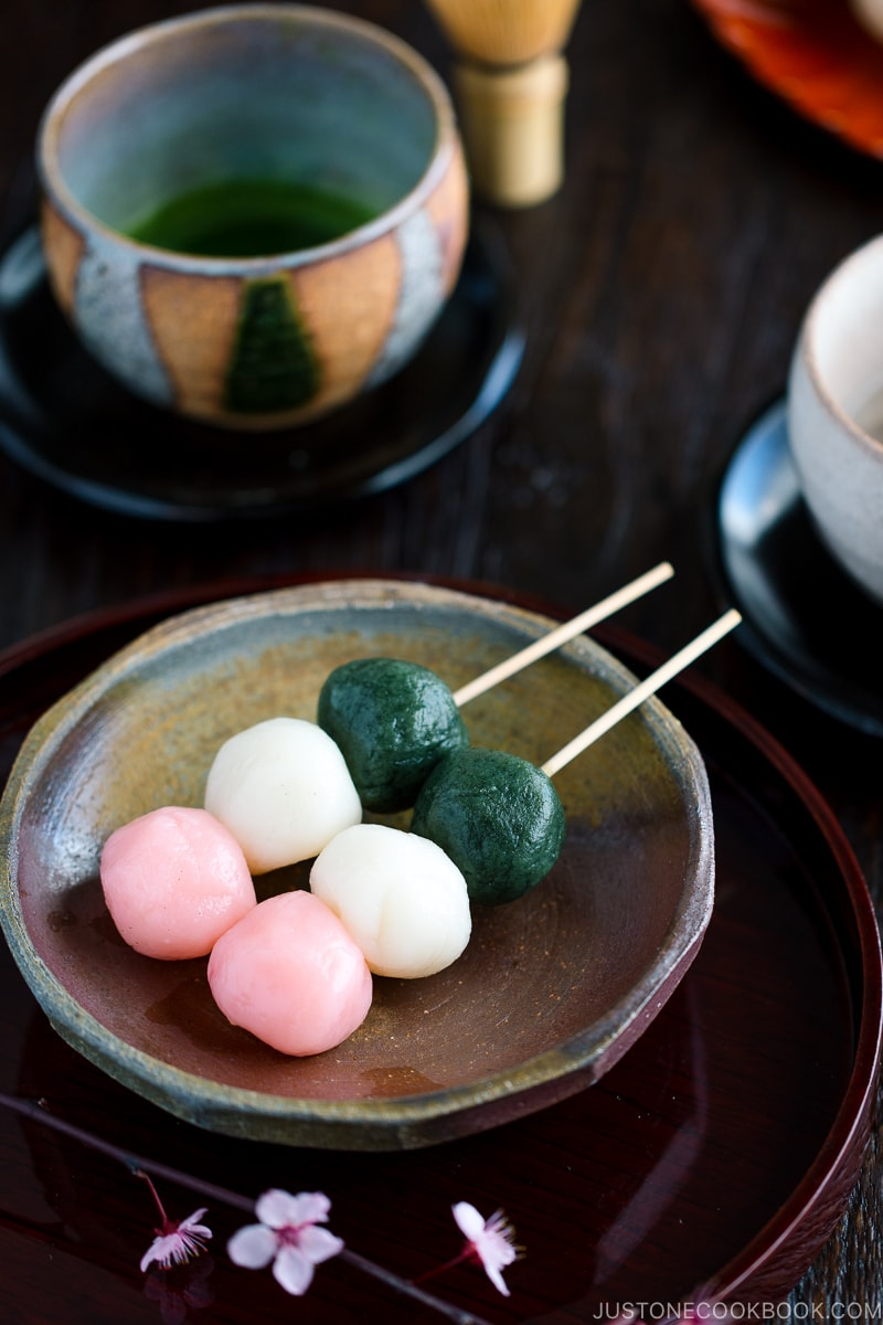 A ceramic plate containing Hanami Dango on a skewer.