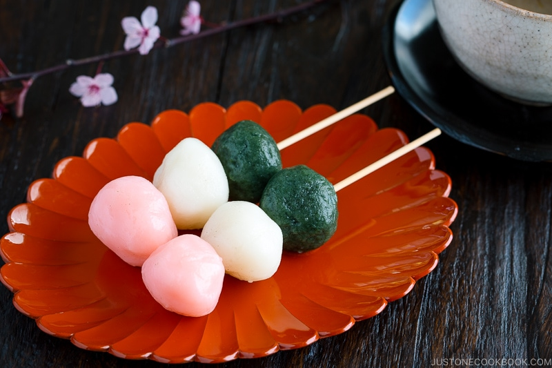 A lacquer plate containing Hanami Dango on a skewer.