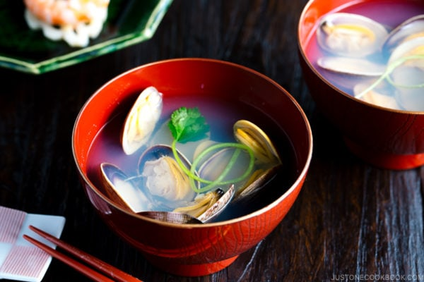 Japanese clam clear soup in a red bowl.