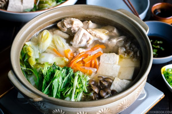 A Japanese earthenware pot (donabe) containing Mizutaki (Japanese Chicken Hot Pot) filled with chicken, tofu, mushrooms, and all kinds of vegetables.