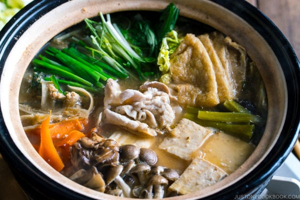 A Japanese earthenware pot (Donabe) containing vegetables, tofu, and pork cooked in sesame and miso based soup broth.