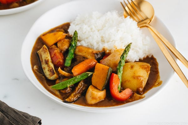 A white plate containing Vegetarian Japanese Curry along with steamed rice.