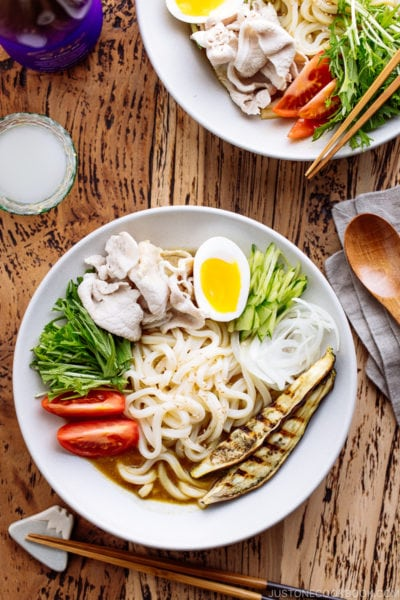 A white bowl containing cold curry udon with sliced pork, boiled egg, and fresh vegetables.