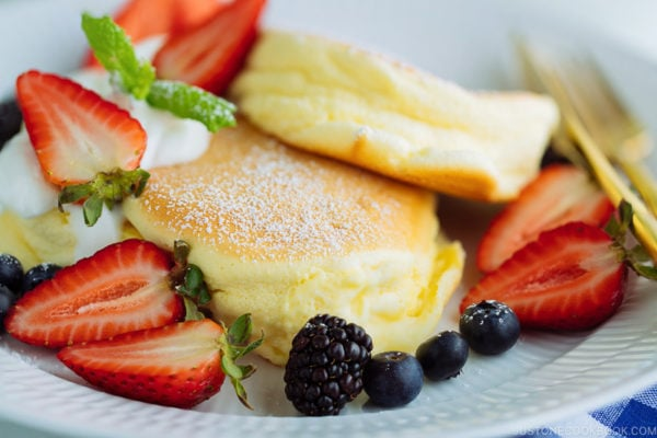 A white plate containing fluffy Japanese souffle pancakes, fresh berries, and whipped cream.