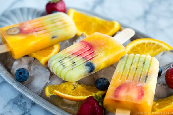 Homemade fruit popsicles on ice cubes.