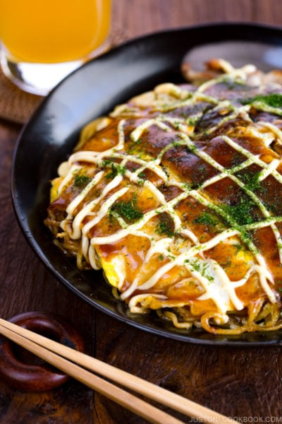 A black plate containing Hiroshima-style OKonomiyaki topped with the savory sauce and Japanese mayo.