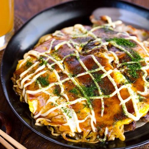 A black plate containing Hiroshima-style OKonomiyaki topped with the savory sauce and Japanese mayo.