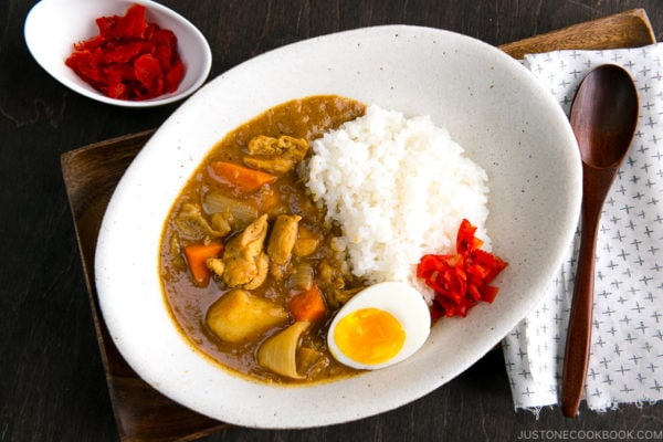A white oval-shaped plate containing Japanese Chicken Curry topped with egg and pickles.