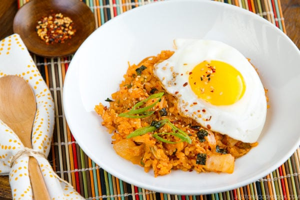 A white plate containing kimchi fried rice with a fried egg on top.