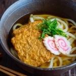 A dark bowl containing Kitsune Udon Noodle Soup.