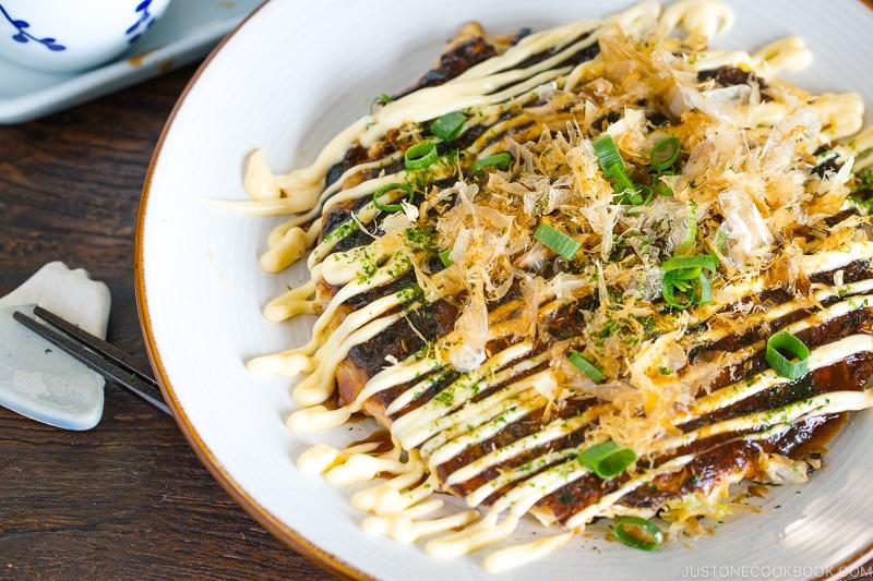 A white plate containing Okonomiyaki, Japanese savory pancake.