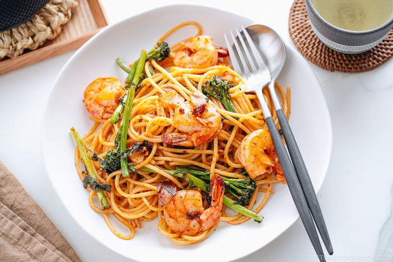 A white plate containing Japanese Pasta with Shrimp and Broccolini.