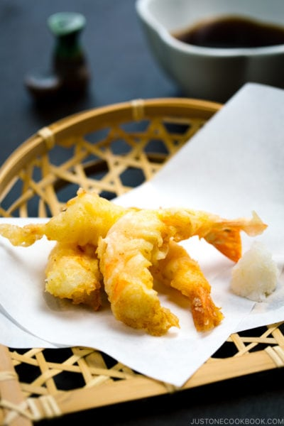 Shrimp tempura on a plate along with the dipping sauce.