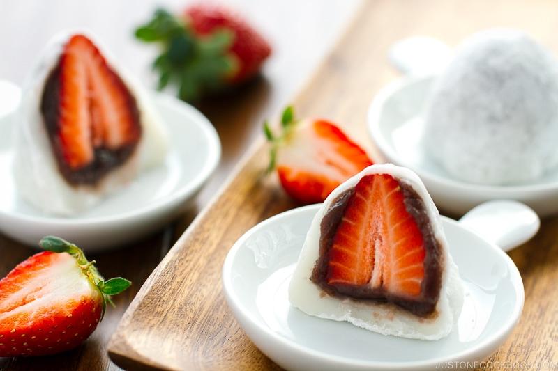 Sliced-in-half Strawberry Mochi (Ichigo Daifuku) on a white plate.