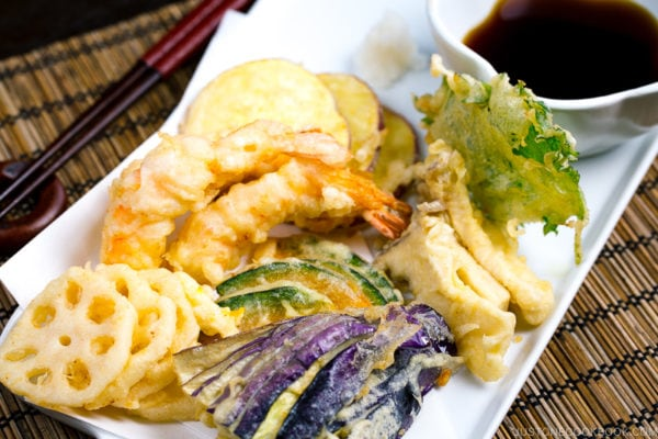 Shrimp and vegetable tempura on a plate along with the dipping sauce.
