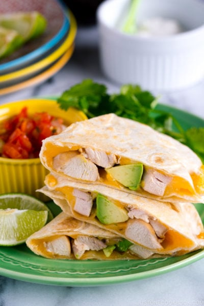 A green plate containing teriyaki chicken quesadilla.