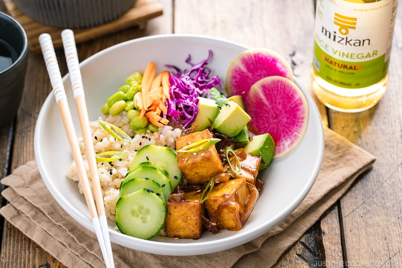 A white bowls containing savory pan-fried tofu, cucumber, avocado, edamame, carrot, red cabbage, and watermelon radish over brown rice.