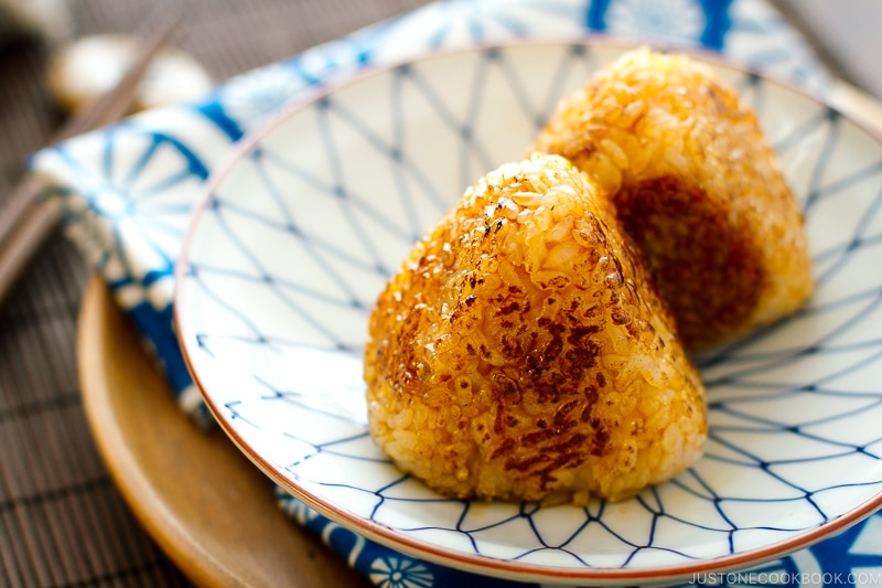 A Japanese blue and white plate containing Yaki Onigiri - Japanese Grilled Rice Balls).