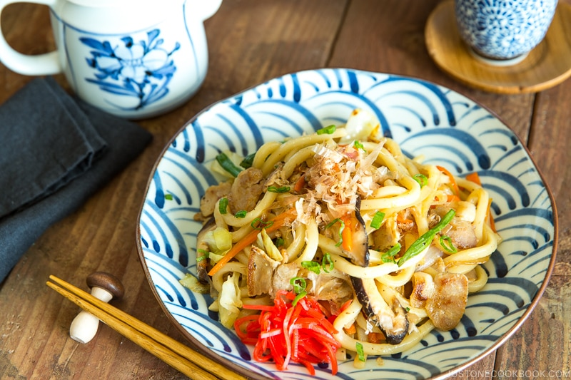 A Japanese blue and white plate containing stir fried udon noodles called Yaki Soba.