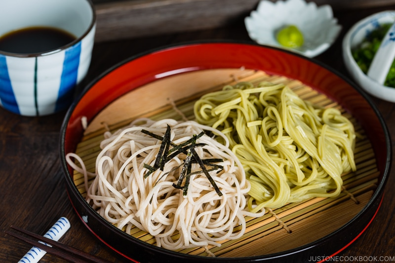 Two kinds of soba noodles served on a Japanese bamboo, garnished with shredded nori sheet.