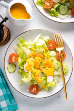 Carrot ginger dressing drizzled on the refreshing iceberg lettuce and cucumber slices.