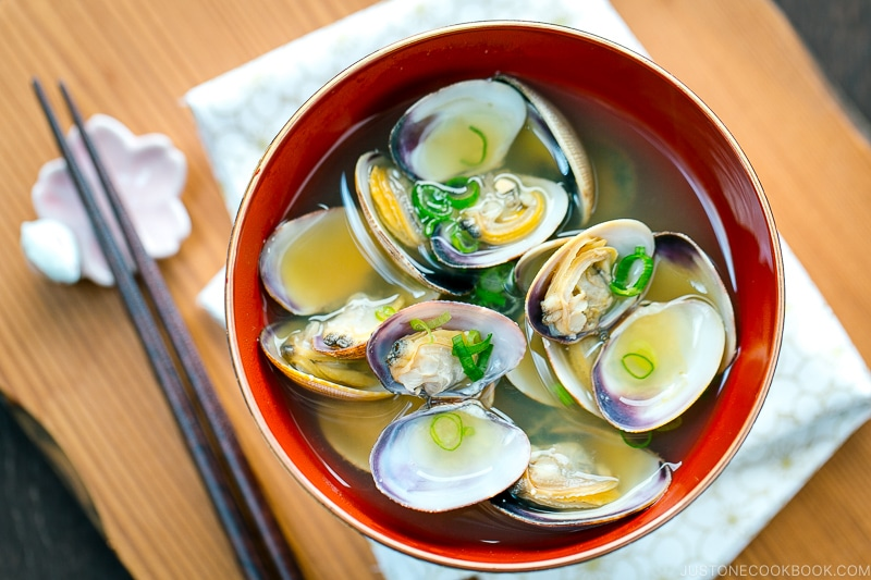 A red bowl containing Clam Miso Soup.