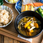 Kabocha Miso Soup served in a black bowl.