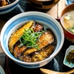 A Japanese rice bowl containing Soy-Glazed Eggplant Donburi topped with julienned shiso and toasted sesame seeds.