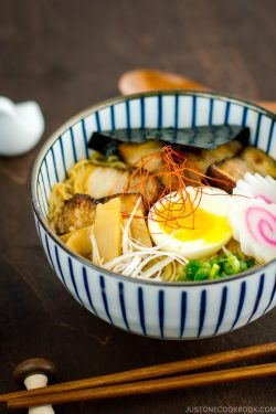 A bowl containing Spicy Shoyu Ramen topped with soft boiled egg, fish cake, nori, and fall-apart tender chashu.
