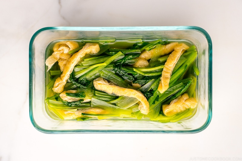 A pyrex container containing Simmered Fried Tofu and Greens.
