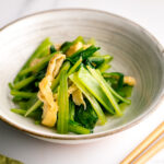 A white Japanese ceramic bowl containing Simmered Fried Tofu and Greens.