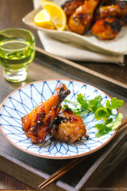 A blue and white plate containing Sweet and Spicy BBQ Chicken Wings.