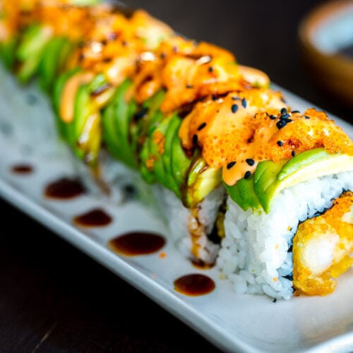 A white plate containing a Dragon Roll.