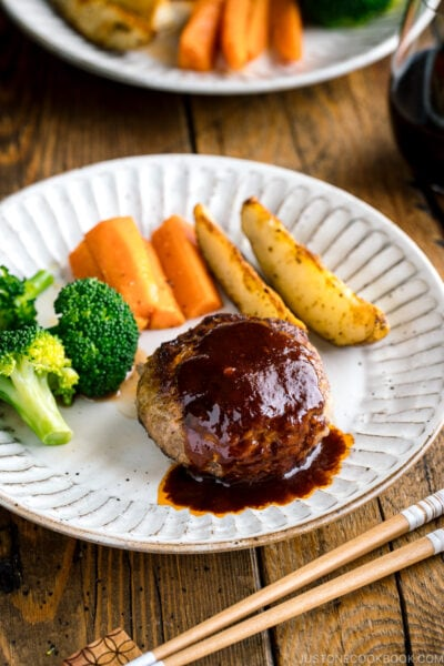 A white plate containing Japanese Hamburger Steak (Hambagu), sautéed carrot, broccoli, and baked potato wedges.