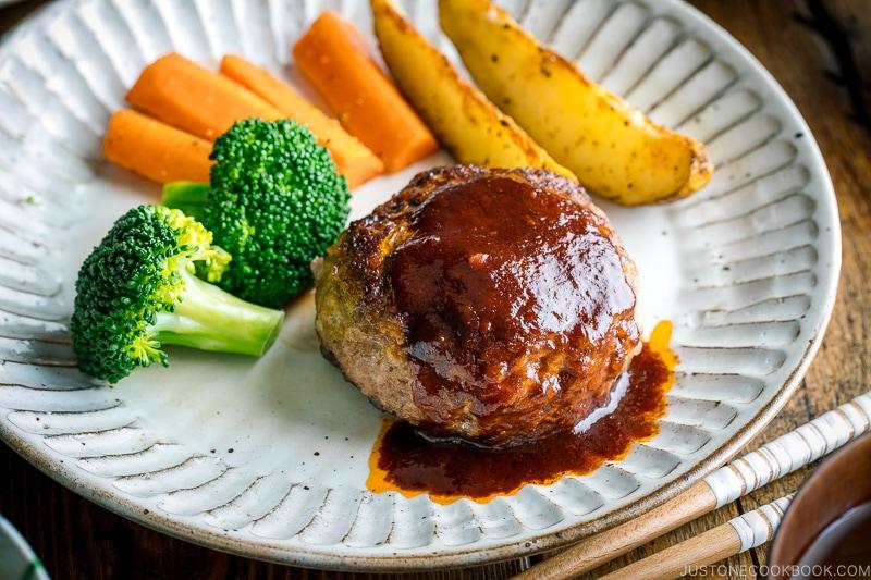 A white plate containing Japanese Hamburger Steak (Hambagu), sautéed carrot, broccoli, and baked potato wedges.