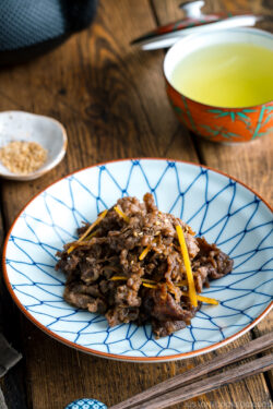 A white and blue Japanese dish containing Simmered Beef with Ginger (Shigureni).