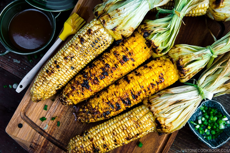 Grilled corn with miso butter sauce on the wooden cutting board.