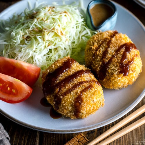 A white plate containing Japanese Croquette (Korokke) served with Tonkatsu sauce and shredded cabbage on the side.