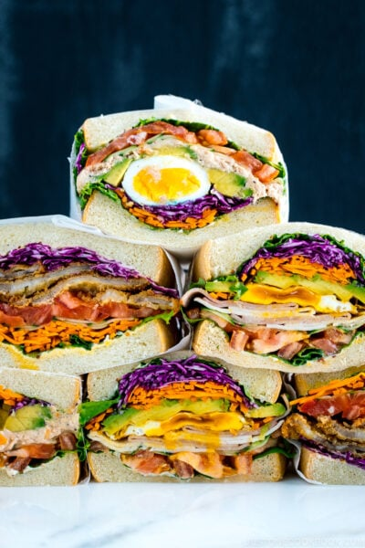 Colorful thick Japanese sandwich, Wanpaku Sandiwch (Sando), shows the filling and piles up on the table.