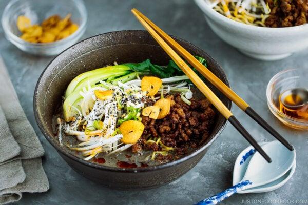 A black bowl containing Black Sesame Dan Dan Noodles.