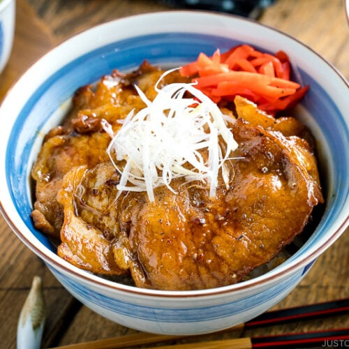 A Japanese bowl containing steamed rice, topped with soy-caramelized pork slices and pickled red ginger.