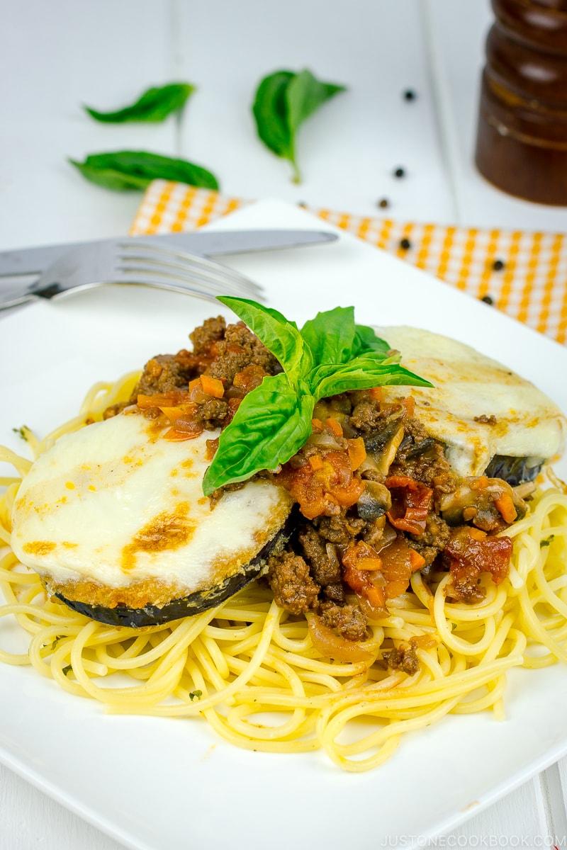 A white plate containing Eggplant Parmesan Spaghetti.