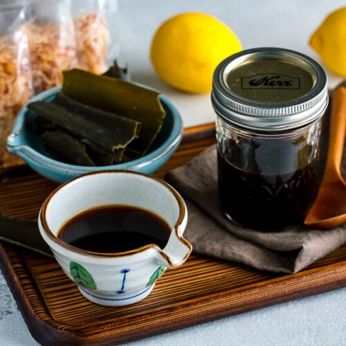 A Japanese ceramic containing Homemade Ponzu Sauce. It's on a tray along with all the ingredients used for the sauce.